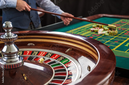 Plakat Roulette and piles of gambling chips on a green table.