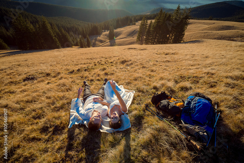 Poster Romantic wedding couple lying on the grass in mountains