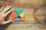 Fototapety man's hand holding a missing piece in a square tangram puzzle, over wooden table.