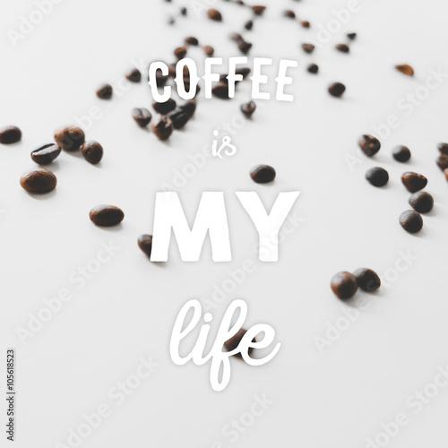ziarna-kawy-rozrzucone-na-stole-i-wyciagniete-recznie-cytaty-kawa-to-moje-zycie