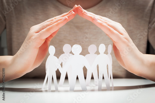 Paper people under hands in gesture of protection.. Concept of insurance