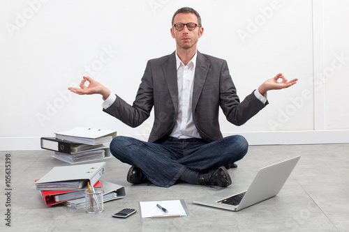 Papiers peints Ecole de Yoga zen business concept - peaceful entrepreneur practicing yoga at the office, sitting crossed legs, seeking for inspiration in working on his budget
