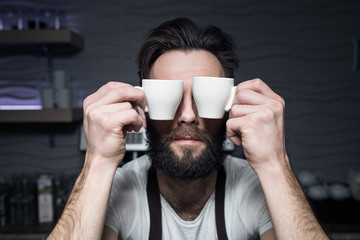 bartender keeps cups of coffee near face;