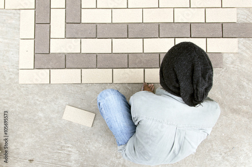 construction mason man hands on tiles work with notched trowel cement mortar Poster