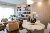 soggiorno in appartamento con tavolo rotondo, libreria a muro e tappezzeria con motivo di farfalle curato e pulito in stile classico  - 105731586