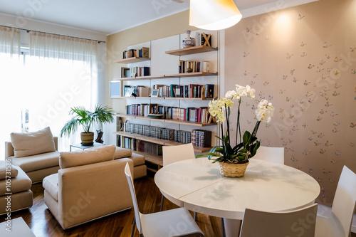 soggiorno in appartamento con tavolo rotondo, libreria a muro e tappezzeria con motivo di farfalle curato e pulito in stile classico
