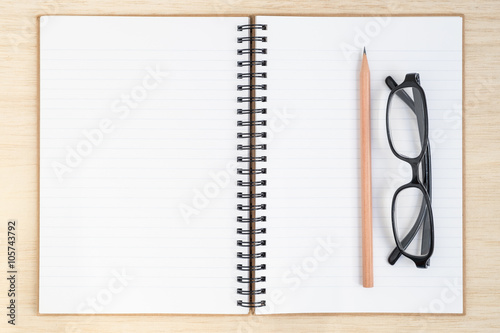 Open spiral notebook on wood background - desk top view Poster