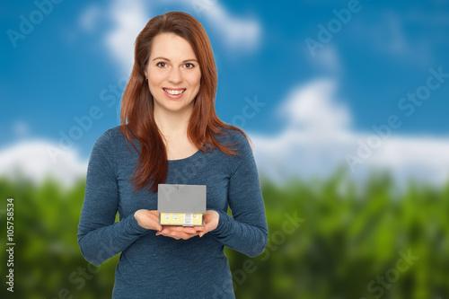 Lachende junge Frau hält ein Haus in ihren Händen Poster