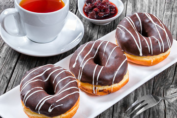 Donuts with Chocolate Icing, a cup of tea, top view