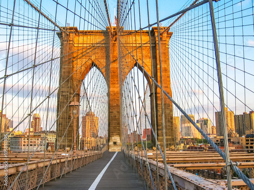 Fototapeta Spectacular views of the Brooklyn Bridge with all its characteristic metal wires and the pedestrian walkway at sunset, New York, United States.
