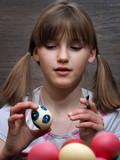 Girl paints eggs. Preparing for Easter