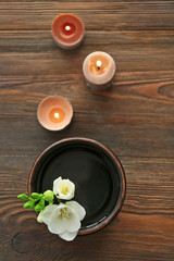 Beautiful flower in the bowl with water and candles on wooden background © Africa Studio