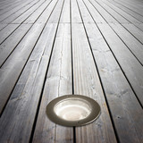 Recessed floor lamp on wooden floor - image with copy space