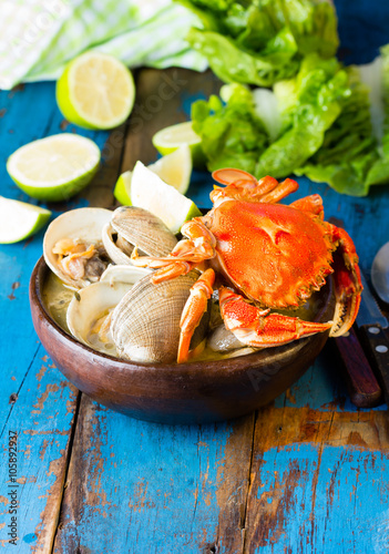 Poster Seafood soup of clams decorated with crab in clay bowl on wooden blue background