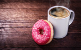 white mug of coffee and a donut on a wooden background