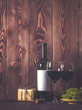Bottle of wine, wineglasses, grape and gift box on wooden table. Retro style. Dark toned