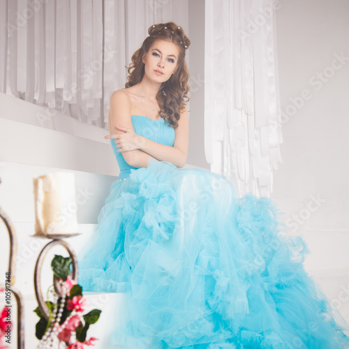 Foto op Plexiglas womenART Beautiful young woman in gorgeous blue long dress like Cinderella with perfect make-up and hair style