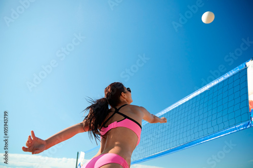 Plakat young woman with ball playing volleyball on beach