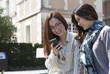 Two women looking at a smart phone with a laugh