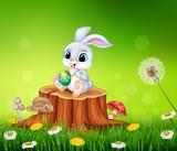 Cartoon Easter Bunny painting an egg on tree stump in summer season background