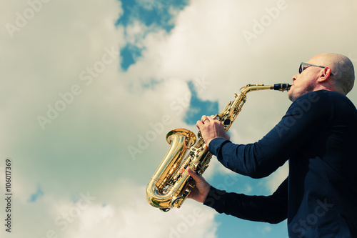 Poster Saxophonist playing on saxophone on blue sky background