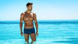 Fototapety Panoramic photo of sexy man posing in swimming pool