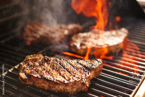 Foto Murales steaks cooking over flaming grill