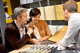 Couple with salesman in kitchen furniture store - 106062582