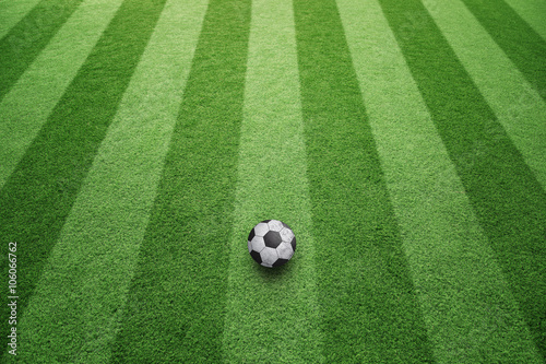 Sunny artificial green football grass with soccer ball background. Soccer game copy space background.