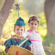 Cute little children dressed up as a fairy and a knight playing in a dreamlike nature