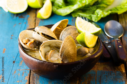 Canvastavla Seafood soup of clams in clay bowl on wooden blue background