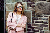 Beautiful fashion model woman wearing sunglasses and standing near brick wall