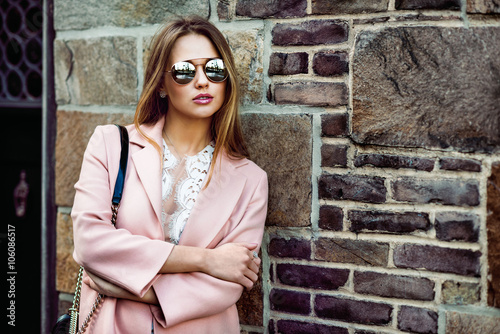 Poster Beautiful fashion model woman wearing sunglasses and standing near brick wall