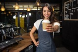 Fototapety Smiling barista holding disposable cup
