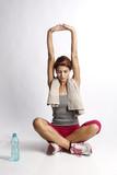 Giovane sportiva con asciugamano al collo che fa stretching con una bottiglietta di acqua in primo pianoi