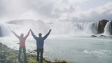 Carefree multiethnic couple raising hands at spectacular Godafoss waterfall. Happy tourists are visiting famous attractions. Man and woman are enjoying vacation at beautiful waterfall in Iceland.