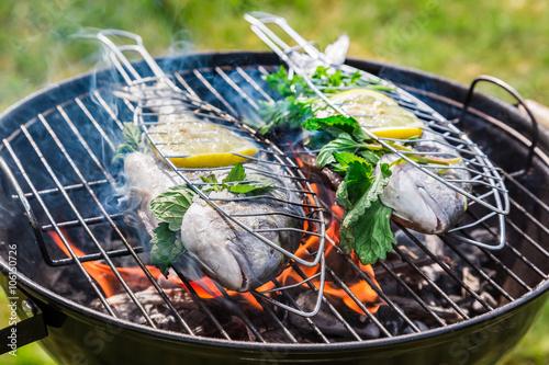 Fototapeta Grilling tasty fish with herbs and lemon