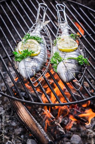 Fototapeta Tasty fish with herbs and lemon for grilling