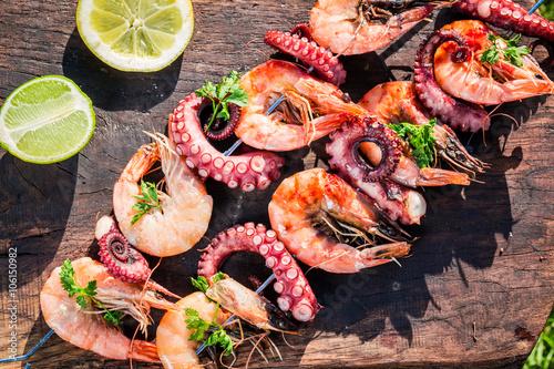Fototapeta Fresh skewers of seafood with lemon and parsley in garden