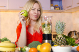 Beautiful young woman next to a blender winking and holding apple in hand, surrounded with fruits and vegetables in kitchen, healthy eating lifestyle concept, preparing smoothie. - 106157732