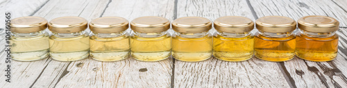Different grade and color of honey in mason jar over wooden background