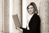 Young business woman with laptop at office building