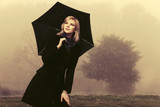 Young fashion woman with umbrella walking outdoor