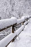 la neve ricopre la staccionata che delimita la strada