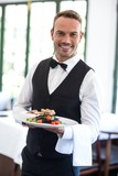 Waiter showing a dish - 106202519