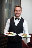 Portrait of waiter presenting meals