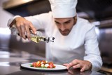 Handsome chef pouring olive oil on meal