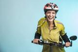 Fototapety Donna Ciclista con casco su sfondo celeste sorride in camera