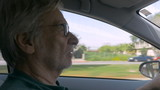 Hand held of an elderly senior man driving a car during the day and talking