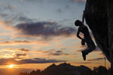 Silhouette of athletic female rock climber climbing steep rock wall against amazing sunset sky in the mountains. Girl is hanging on one hand and holding hand in magnesium bag.